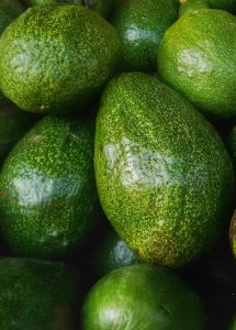 Pile of green Avocados. One of them is opened that the stone and the pulp are visible.